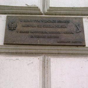 """Tablica """"szkolna"""" (zBiałym Orłem iznakiem """"Rodła"""") naDomu Polskim wOlsztynie"""