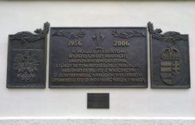 Tablica upamiętniająca wydarzenia z 1956 roku, z herbami Polski i Węgier, wmurowana w ścianę gmachu Starostwa Powiatowego w Olsztynie (u góry wizerunek dwóch skrzyżowanych flag, podobnych do ustawionych podczas wiecu w dniu 30 października 1956 roku) (fot. Radosław Nojman)