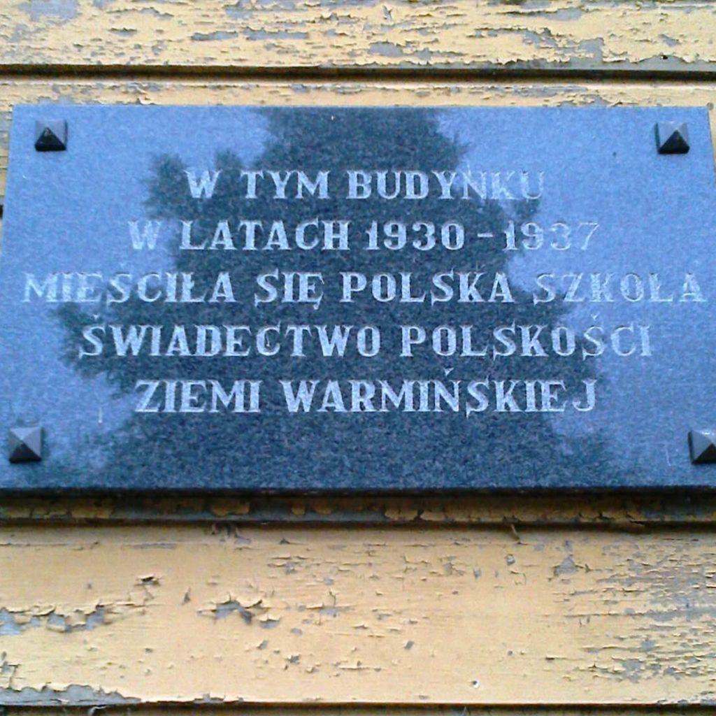Tablica nabudynku dawnej szkoły polskiej wPluskach