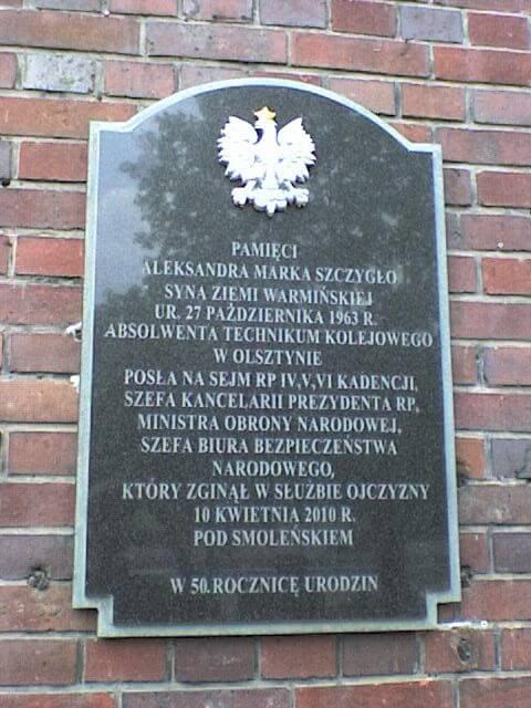 Tablica upamiętniająca A. Szczygło nabudynku Zespołu Szkół Samochodowych im.por. A. M. Bocheńskiego (dawniej Technikum Kolejowego) wOlsztynie