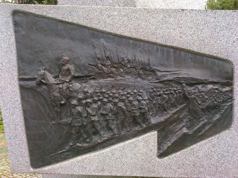Wojsko Polskie zNaczelnym Wodzem Józefem Piłsudskim iksiędzem Ignacym Skorupką naczele (detal zpomnika Polaków internowanych w1920 roku wOrzyszu)