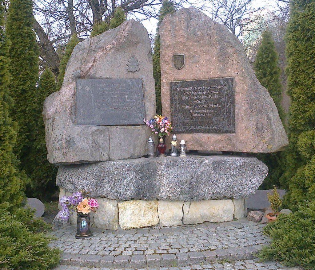 Olsztyński obelisk, stojący naskraju Parku im.Janusza Kusocińskiego, upamiętniający odprawioną przezPapieża-Polaka Mszę Świętą